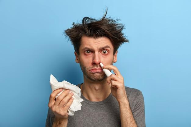 Tratamiento en el hogar, virus, enfermedades estacionales y concepto de alergia. hombre insatisfecho esteriliza la nariz tapada, se resfría, sostiene un pañuelo, tiene fiebre, ojos rojos hinchados, posa contra la pared azul.