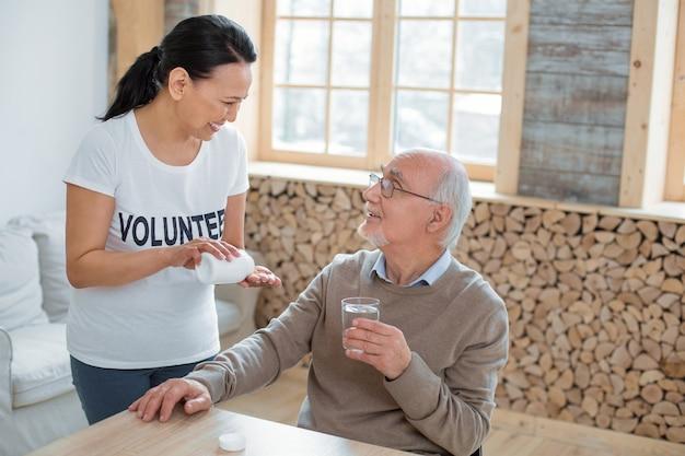 Tratamiento médico. feliz voluntario optimista de pie mientras se ríe con un hombre mayor que sostiene un vaso de agua