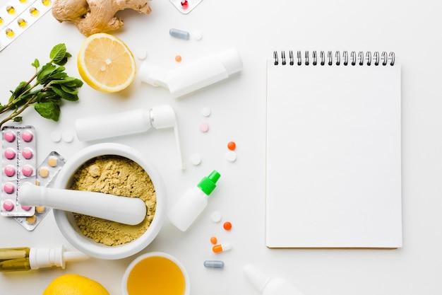 Tratamiento natural y pastillas de farmacia con bloc de notas