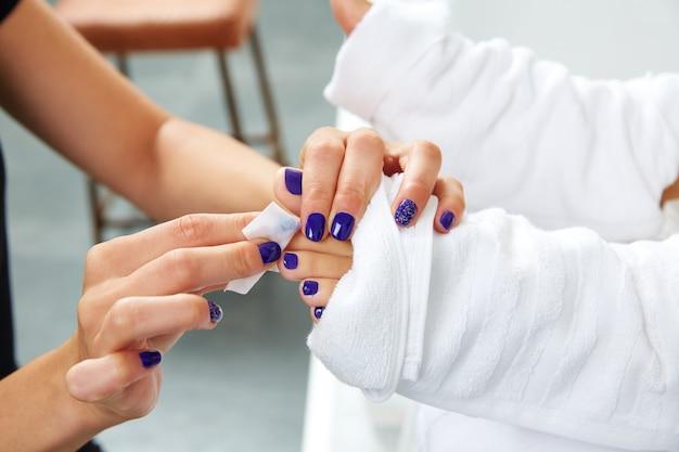 Tratamiento de pedicura para pies de mujer en salón de uñas.