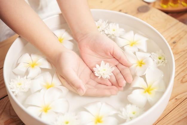 Tratamiento y producto de spa. flores blancas en cuenco de cerámica con agua para aromaterapia en el spa.