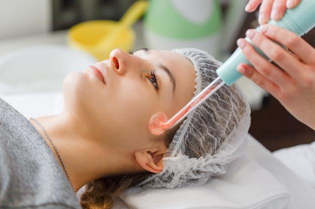 Tratamiento de rayos violeta en la cara de la esteticista.