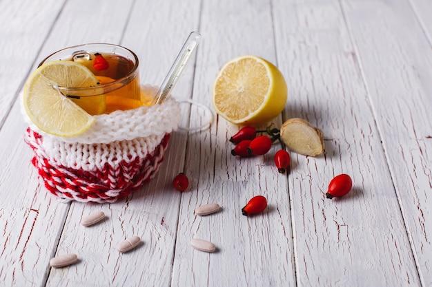 Tratamiento del resfriado. la taza con té caliente con el limón y las bayas se coloca en una tabla