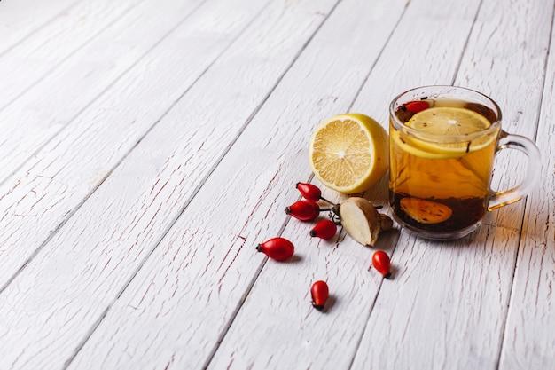 Tratamiento del resfriado. té caliente con limón y bayas se encuentra en mesa de madera blanca