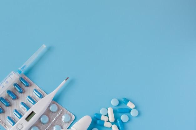 Tratamiento de resfriados y gripe. varios medicamentos, un termómetro, aerosoles de la nariz tapada y un dolor en la garganta sobre un fondo azul. copia espacio medicina plana