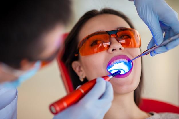 Tratamiento del sello de luz de niña hermosa en odontología.