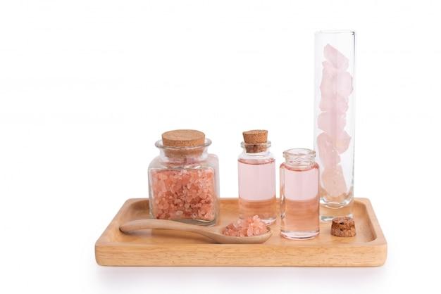 Tratamiento de spa con jabón líquido, sal rosa y piedras en la bandeja de madera aislada en blanco con la ruta