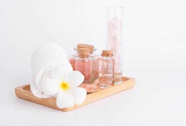 Tratamiento de spa con jabón líquido, sal rosa, piedras y flor de plumeria en bandeja de madera sobre blanco