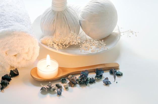 Tratamientos de spa con bola de compresión a base de hierbas, velas y toalla