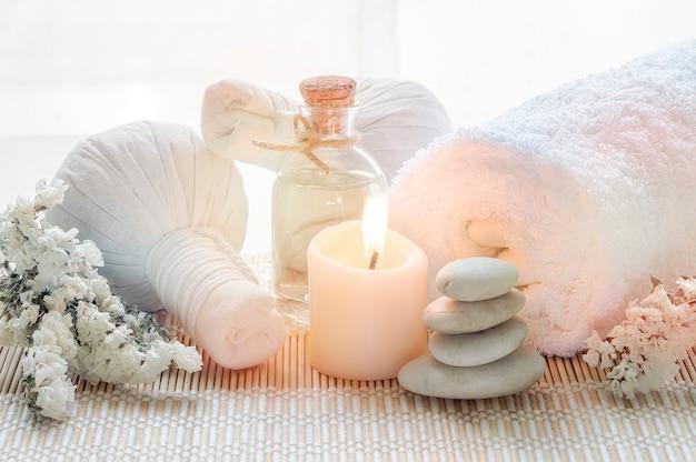 Tratamientos de spa con bola de compresión de hierbas, botella de aceite, velas y toalla.
