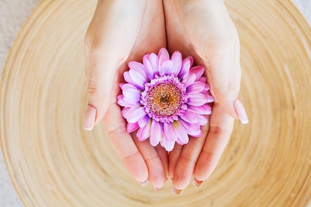 Tratamientos de spa. mujer sostenga hermosa flor en sus manos
