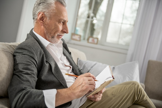 Trate de ser serio. pensionista positivo sentado en casa y mirando hacia adelante mientras toma notas