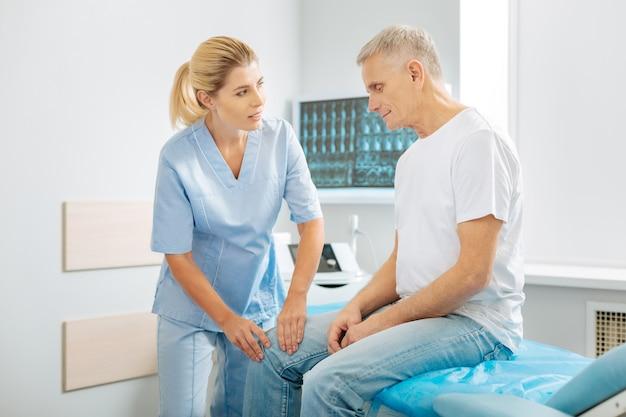 Trato profesional. terapeuta agradable amable positivo de pie cerca de su paciente y hablando con él mientras revisa su pierna