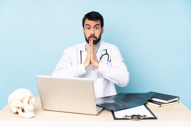 El traumatólogo profesional en el lugar de trabajo mantiene la palma unida. la persona pide algo