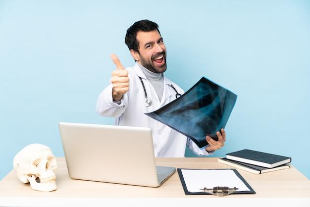 Traumatólogo profesional en el lugar de trabajo con el pulgar hacia arriba porque algo bueno ha sucedido