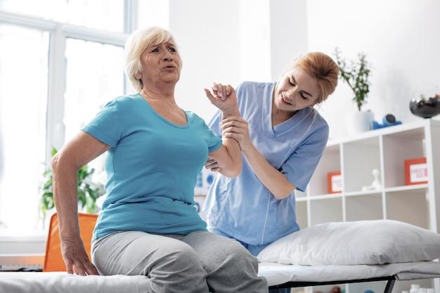 A través del dolor. agradable mujer senior sintiendo dolor mientras levanta la mano