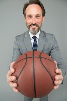 Las trayectorias profesionales de los entrenadores comienzan aquí. entrenador de baloncesto fondo gris. entrenador de negocios mantenga la pelota de baloncesto. entrenador feliz o entrenador en ropa formal. coaching y docencia. aprenda de los hechos.