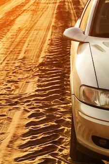Traza de ruedas y coche en una carretera