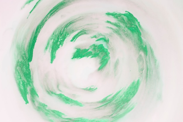 Trazos de pintura verde artística en forma circular sobre fondo blanco