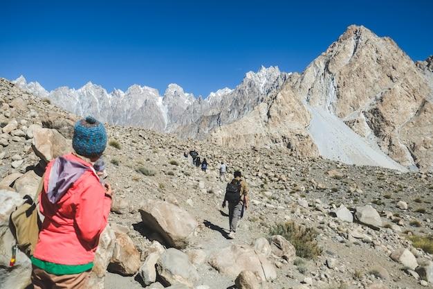 Trekkers caminando por la pista en passu, gilgit baltistan, pakistán.