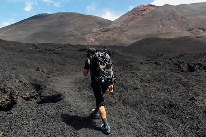 Trekking en el pico del volcán.hiker escalada en el volcán del cráter etna en sicilia