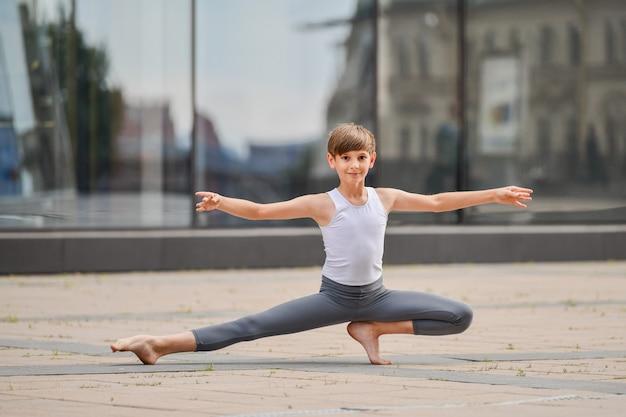 Tren de adolescente de niño de ballet de pie en sus manos contra el fondo del reflejo de la ciudad y el cielo en la pared de vidrio