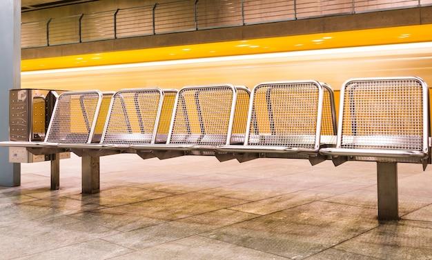 Tren amarillo a exceso de velocidad en el metro subterráneo detrás de bancos de metal en espera