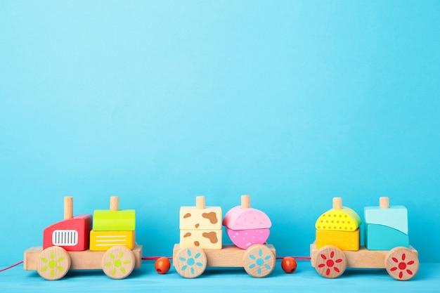 Tren de apilamiento de juguete para niños pequeños en azul con reflejo de sombra. tren bebé fabricado con bloques geométricos de madera. tren apilable de madera colorido para niños