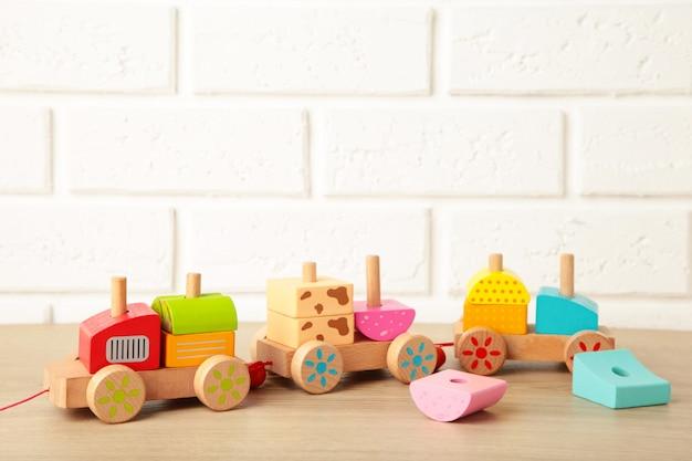 Tren de apilamiento de juguete para niños pequeños en luz con reflejo de sombra. tren bebé fabricado con bloques geométricos de madera. tren apilable de madera colorido para niños