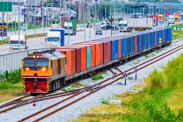 Tren de carga del envase con el funcionamiento a través del districto industrial, el puerto.