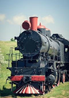 Tren clásico viejo al tubo rojo sobre un fondo de hierba verde.