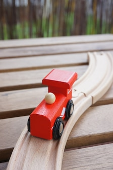 Tren de juguete rojo de madera sobre vías de madera