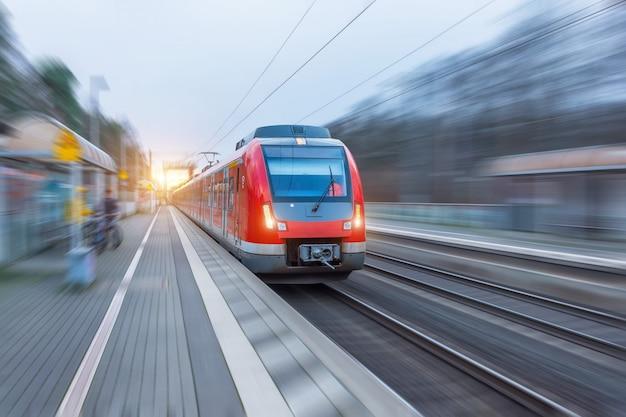 Tren rojo de alta velocidad del pasajero con el desenfoque de movimiento en la estación.