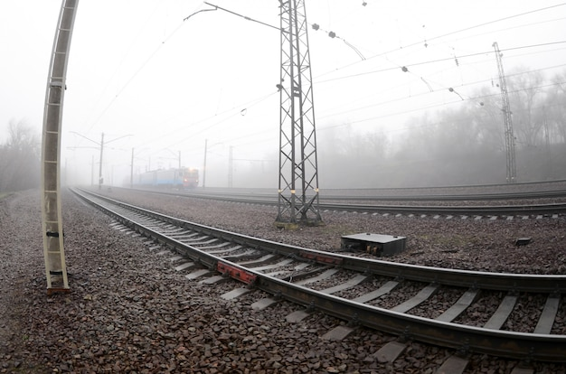 El tren suburbano ucraniano corre a lo largo del ferrocarril en una mañana brumosa