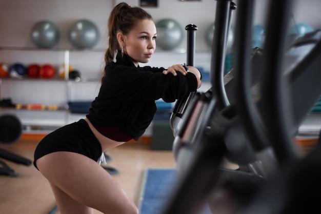 Trenes de la mujer en una cinta de correr en el gimnasio. muchacha de la aptitud que presenta en la máquina de la rueda de ardilla.