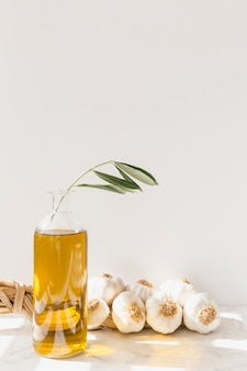 Trenza de bulbo de ajo con botella de aceite de oliva contra la pared blanca