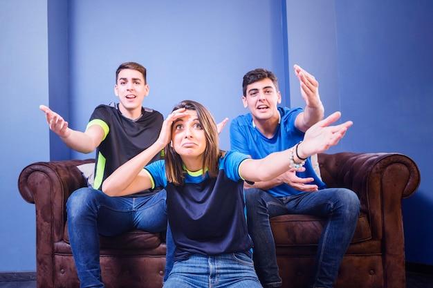 Tres aficionados en sofá no se lo pueden creer