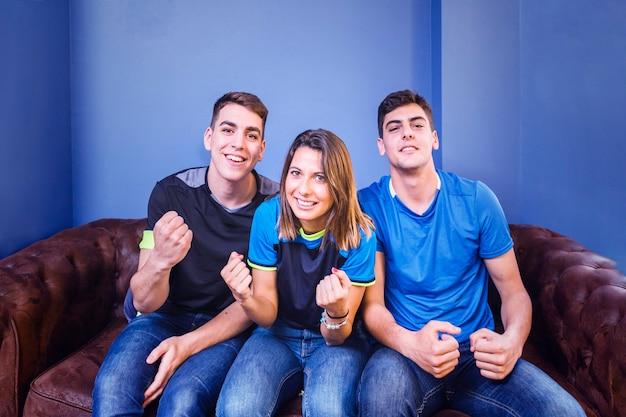 Tres aficionados en sofá