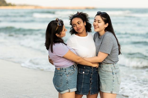 Tres amigas abrazados en la playa
