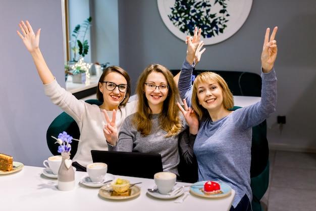 Tres amigas bonitas con las manos en alto divirtiéndose y comiendo postres en una panadería o pastelería, usando una computadora portátil para su trabajo u ocio