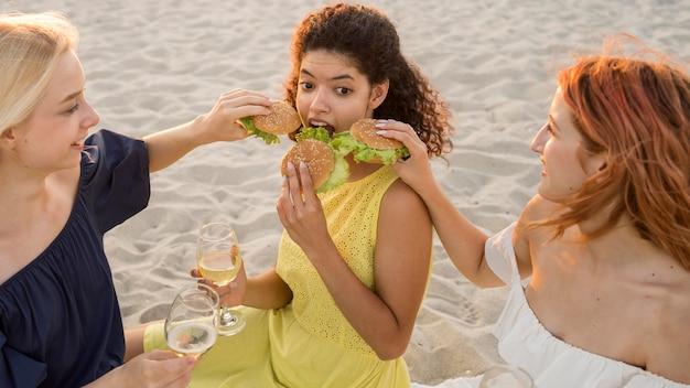 Tres amigas comiendo hamburguesas en la playa.