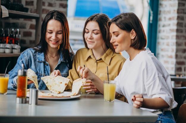 Tres amigas comiendo pizza en un bar