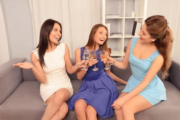 Tres amigas jóvenes atractivas celebrando con champán y tintineo