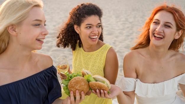 Tres amigas sonrientes disfrutando de hamburguesas juntos en la playa
