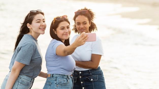 Tres amigas tomando selfie en la playa con espacio de copia