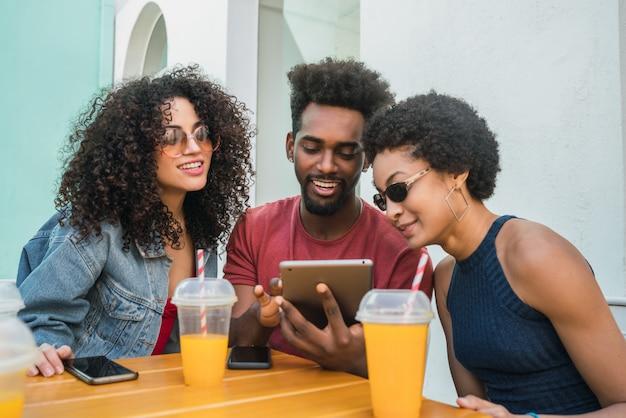 Tres amigos afro con tableta digital.
