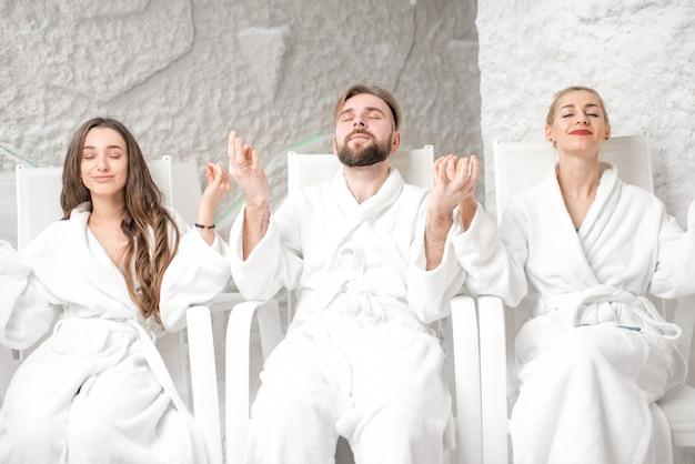 Tres amigos en albornoces meditando en la sala de sal.