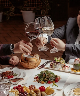 Tres amigos animan copas de vino con vino tinto y blanco en la cena