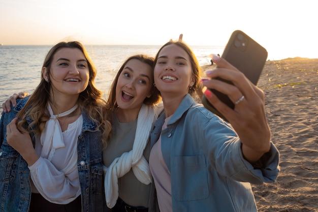 Tres amigos caminan por la playa la felicidad de la comunicación.