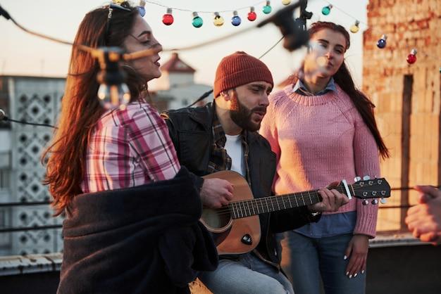 Tres amigos disfrutan cantando canciones de guitarra acústica en la azotea